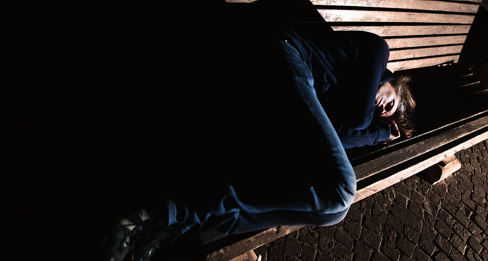 Homeless girl sleeping on a bench in the night mysterious atmosphere